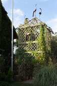 Tower-shaped lattice pavilion covered in climbing plants and decorated with bird ornaments