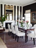 White, upholstered chairs and table in front of fireplace in dining room with black and white striped wallpaper