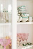Crockery and glasses in white, shabby-chic, glass-fronted cabinet