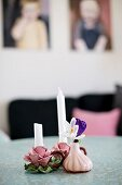 Crocuses in small vase next to candle holders shaped like roses