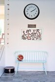 Wooden bench painted pastel blue below child's drawing and station clock on wall