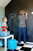 Child drawing on wall painted with blackboard paint