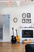 Guitars next to open fireplace below framed family photos in rustic living room