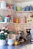 Pastel, retro crockery on shelving decorated with fairy lights above kitchen counter