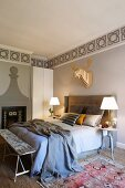 Double bed with upholstered headboard, table lamps on bedside tables, stencilled frieze on wall and stylised hunting trophy
