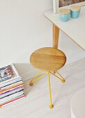 Designer stool with yellow wire frame, china pots with wooden lids on table and stacked magazines on floor
