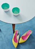 Tea bowls with mint-green interiors on delicate side table and bright yellow high heels on rug