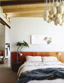 'Eggs' designer lamp and portrait artwork above modern bed with headboard in bedroom with ensuite bathroom in background