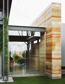 Modern house with steel and glass facade and wall slab with rammed-earth structure