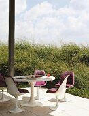 Tulip chairs and table on secluded, sunny terrace adjoining plant covered hill