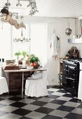 Rustic kitchen with chequered floor, chairs with loose white covers at dining table in front of window and vintage cooker to one side