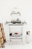 Crockery and silver pots on ornamental shelving on delicate side table made from white-painted wood