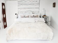 Fur blanket and bolster on double bed with carved wooden headboard against white horizontal boards on wall