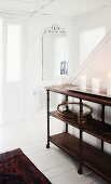 Candles on dark, half-height wooden shelves against staircase in white, wood-clad foyer
