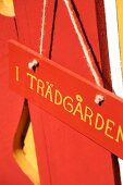 Swedish motto on sign hanging on red-painted facade of wooden house