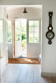 Hallway in Swedish wooden house with half-open French doors and antique barometer on wall