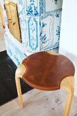 Scandinavian, laminate-wood stool with leather seat in front of antique tiled stove with classic blue and white pattern