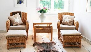 Side table flanked by wicker armchairs and foot stools below window