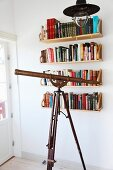 Retro pendant lamp above antique telescope in front of books on wall-mounted shelves