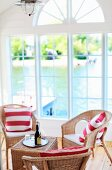 Rattan armchairs with red and white striped cushions; view of Swedish Skerry coast through lattice windows