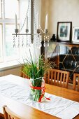 Candle chandelier with white candles above glass vase of ornamental grasses and white runner on wooden dining table