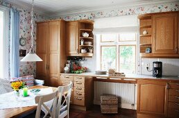 Dining area in kitchen with solid wooden, country-house-style fitted cabinets