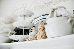 Cake stand made from white, china plates, small figurine and pot on shelf