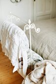 Ornate, white-painted, metal valet stand at foot of bed