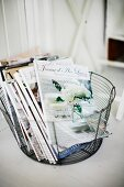 Wire basket of magazines on floor