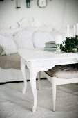 Candles on white-painted coffee table with curved legs and upholstered footstool in front of sofa