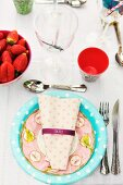 Pastel patterned paper plate and napkin on place setting for garden party