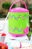 Drinks dispenser with cheerful pattern and tap on table in garden