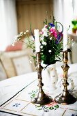 White candles in brass candlesticks and vase of garden flowers on table with tablecloth