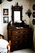 Antique chest of drawers with dresser mirror in corner surrounded by framed photos of children on walls