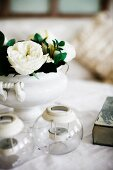 Tealight holders and white roses in china vase