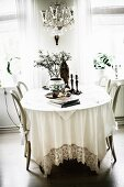 Table with white tablecloth and chairs with curved backrests in rustic dining room