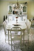 White dining set; chairs with seat covers around oval table below candle chandelier