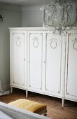 Elegant, antique cabinet on slim feet painted white and with carved doors in bedroom