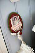 Vintage arrangement of lace textile hanging from painted, wooden wall hook