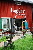 Clothes shop in Falu-red, rustic wooden house with open doors; clothes rack and sewing machine on lawn in foreground