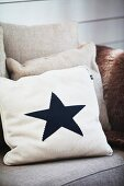 Pale scatter cushion with black star motif on sofa