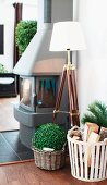 Standard lamp with maritime, tripod base and basket of firewood next to wood-burning stove