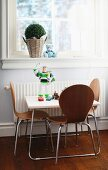 Children's table and engineered wood chairs with steel tube frames below window