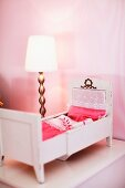 Old dolls' bed with lace bed covers and lamp with brass base on bedside table