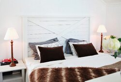Double bed with half-height headboard made from wooden boards flanked by simple, Shaker-style lamps