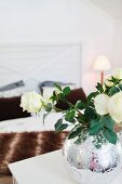 White roses in round, ornate, mercury glass vase; double bed in background