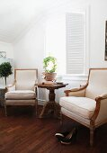 Period armchairs with ecru upholstery, wicker side table and window with interior folding shutters