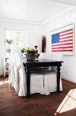 Stars and Stripes artwork in dining area with black, antique wooden table and chairs with loose covers in white, country-house interior