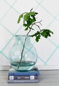 Branch of leaves in glass vase on stacked books against wall decorated with diamond pattern of washi tape