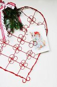 Red, wire ornamental heart with clips for displaying Christmas cards